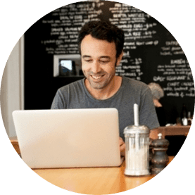 man sitting at a cafe with laptop